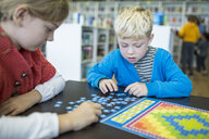 Pupils playing a board game in school library - WESTF24086