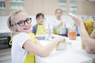 Portrait of smiling schoolgirl with classmtes in cooking class - WESTF24089