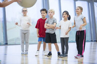 Pupils in gym class looking at teacher - WESTF24098