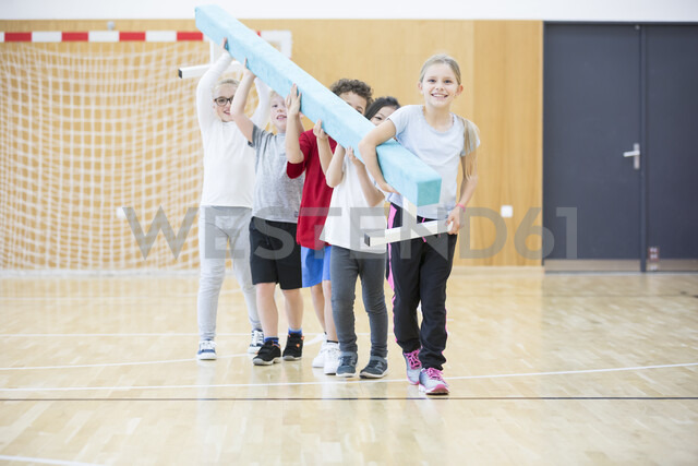 Pupils carrying balance beam in gym class - WESTF24101