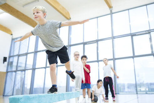 Schoolboy balancing on balance beam in gym class - WESTF24104