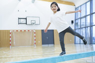 Schoolgirl balancing on balance beam in gym class - WESTF24107