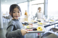 Portrait of smiling schoolgirl carrying tray in school canteen - WESTF24110