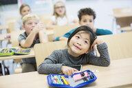 Portrait of schoolgirl with classmates in class - WESTF24113