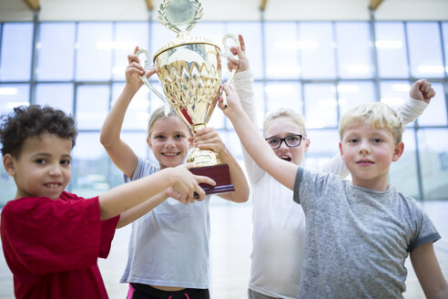 Happy pupils holding trophy in gym - WESTF24116