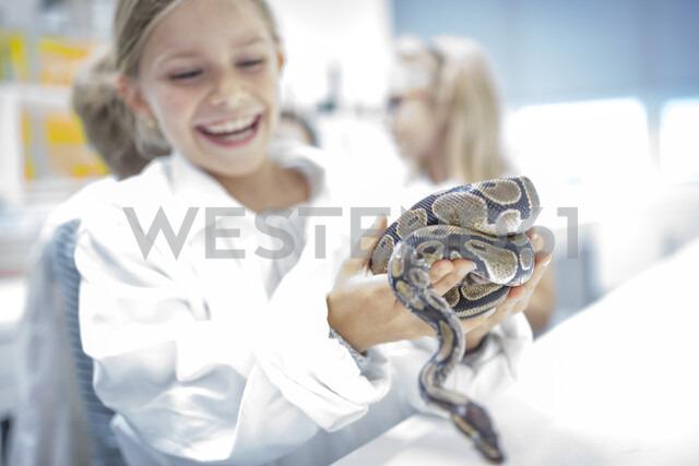 Happy schoolgirl in science class holding snake - WESTF24122