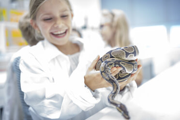 Happy schoolgirl in science class holding snake - WESTF24122