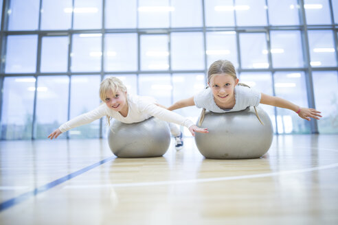 Portrait of smiling schoolgirls balancing on gym balls in gym class - WESTF24131