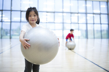 Portrait of smiling schoolgirl holding gym ball in gym class - WESTF24134