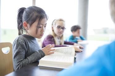 Schoolgirl reading book on table in school break room - WESTF24140