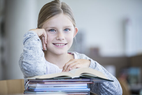 Portrait of smiling schoolgirl with books in school - WESTF24146