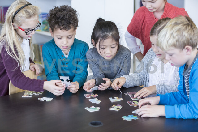 Pupils playing jigsaw puzzle in school together - WESTF24149
