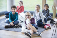 Portrait of smiling pupils sitting on the floor in school break room - WESTF24152