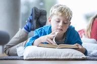 Schoolboy lying on the floor reading book in school break room - WESTF24155