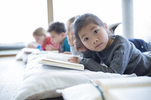 Portrait of schoolgirl lying on the floor with classmates reading book in school break room - WESTF24161