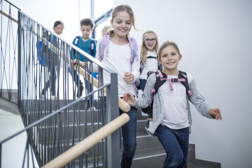 Happy pupils on staircase leaving school - WESTF24170