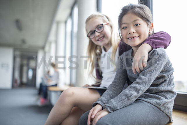 Portrait of two smiling schoolgirls sitting on school corridor - WESTF24176