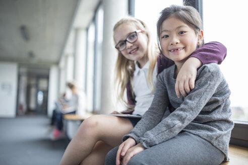Portrait of two smiling schoolgirls sitting on school corridor - WESTF24176