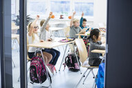 Happy pupils raising their hands in class - WESTF24203