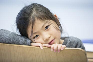 Portrait of schoolgirl on chair in school - WESTF24212