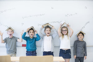 Happy pupils with books above their heads standing at whiteboard with formulas in class - WESTF24215