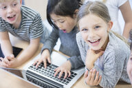 Happy pupils using laptop in class - WESTF24218