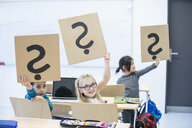 Pupils with laptop in class holding up cardboards with question marks - WESTF24221