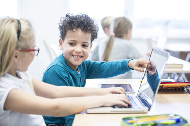 Schoolboy and schoolgirl using laptop together in class - WESTF24224