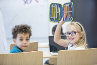 Portrait of schoolboy and schoolgirl with laptop and pencil case in class - WESTF24227