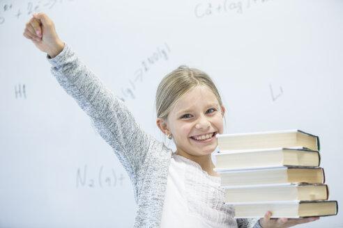 Portrait of happy schoolgirl carrying books in class - WESTF24230
