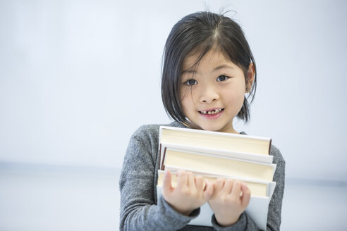Portrait of smiling schoolgirl carrying books in class - WESTF24233
