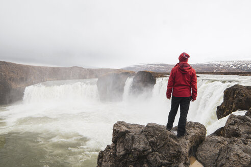 Iceland, man standing at Godafoss waterfall - KKAF01035