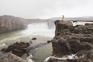 Iceland, woman standing at Godafoss waterfall - KKAF01038