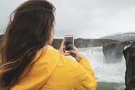 Iceland, woman taking cell phone picture of Godafoss waterfall - KKAF01041