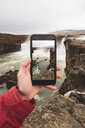 Iceland, hand holding cell phone with picture of Godafoss waterfall - KKAF01044