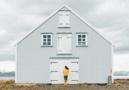 Iceland, woman with guitar standing at lonely house - KKAF01047