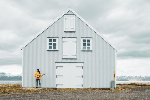Iceland, woman playing guitar at lonely house - KKAF01050