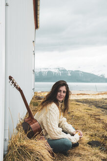 Iceland, woman with guitar sitting in rural landscape - KKAF01053