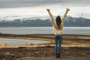 Iceland, woman standing at lakeside with raised arms - KKAF01059