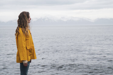 Iceland, woman standing at the sea - KKAF01065