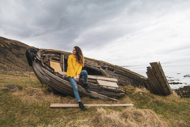 Iceland, woman in boat wreck at the coast - KKAF01068