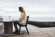 Iceland, woman using laptop at the sea - KKAF01074