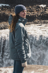 Iceland, woman standing at Dettifoss waterfall - KKAF01083