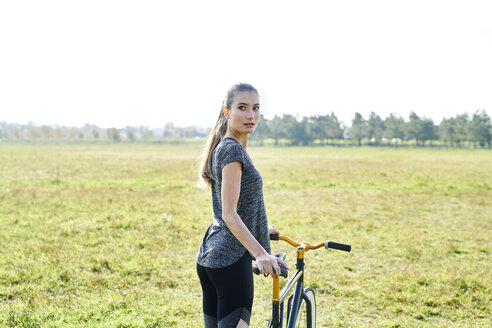 Sportive young woman with bicycle on a meadow - MMIF00084