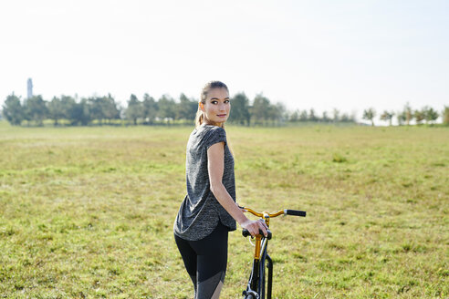 Sportive young woman with bicycle on a meadow - MMIF00087