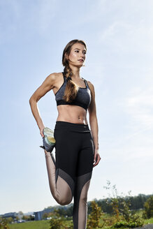 Sportive young woman stretching her leg - MMIF00096