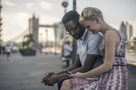 Young couple sitting on wall, looking at smartphone, Tower Bridge in background, London, England, UK - ISF05798