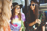 Three young boho women wearing sunglasses in recreational van - ISF05813