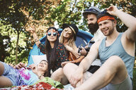 Five young adult friends playing acoustic guitar while festival camping - ISF05819