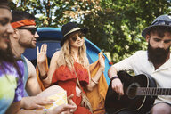 Young adult friends playing acoustic guitar while festival camping - ISF05822